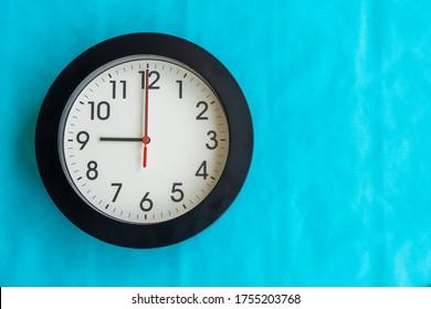 Eine schwarz-weiße Uhr an der blauen Wand