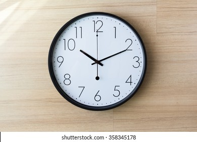 black and white clock on light wooden wall with shiny on the wall, ten past ten o'clock concept : late appointment, late morning, wake up late,
