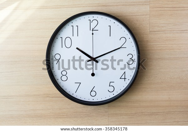 schwarz-weiße Uhr an hellhölzerner Wand mit glänzender Wand, zehn Uhr Konzept: später Termin, später Morgen, spät aufwachen,