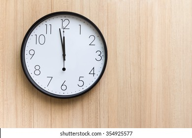 black and white clock shown almost mid day or mid night time on light wooden wall ,free space for text  concept : countdown for new year