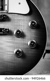 Black and White Close Up of the Corner of a Sunburst Electric Guitar with the Knobs, Pick Guard and PIckups