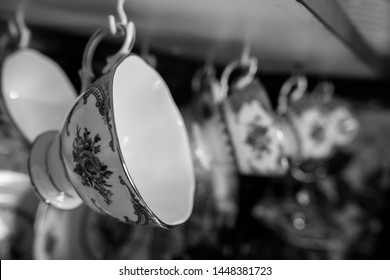 Black and white close up of a fine china teacup hanging in a row of teacups in a cabinet, blurred background. Chic interior. Retro, vintage.
