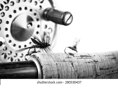 Black and White Close up of fly fishing lure, rod and reel on white background