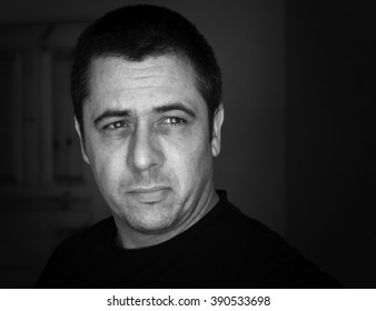 Black and White close up head portrait image of a handsome young middle aged man in his forties looking off the edge of a frame at an unknown object. Added monochrome vignette and copy space area