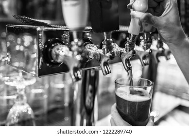 A black & white, close up image of a bartender pouring beer from a tap into a pint glass.