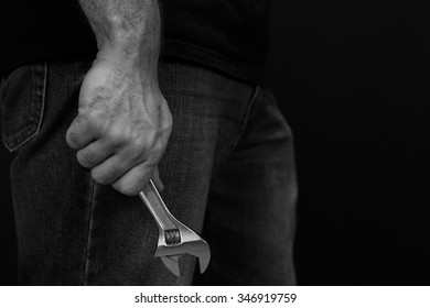 Black and white close up image of a man in jeans and a t shirt holding a wrench at his side in front of a black background.