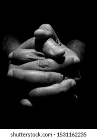 Black an white close up of a mans clasped hands in low key lighting