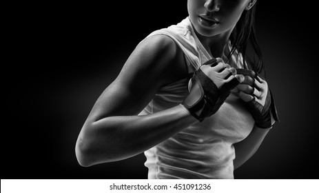 Black and white close up portrait of fitness athletic young woman in sports clothing showing her well trained body, six pack, perfect abs, shoulders, biceps, triceps and chest, deltoid muscle.