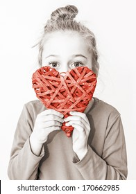 Black and white, close up portrait of five years old caucasian blond child girl holding red heart symbol on a white background. Love, Valentine's Day or charity concept.
