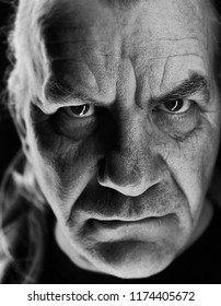 black and white close up portrait of an older male with dark evil horror expression on face, menacing high contrast.