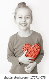 Black and white, close up portrait of smiling five years old caucasian blond child girl holding red heart symbol on a white background. Love, Valentine's Day or happy childhood concept.