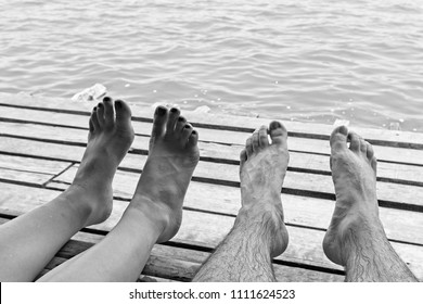 A black and white close up shot of a Caucasian couple's feet while sitting on a jetty. This image can be used to represent love between two people.