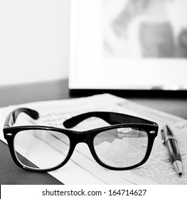 Black and white close up still life of a pair of reading glasses and a pen on an orange financial newspaper on a dark wooden writing desk with a family photo frame. Office interior with no people.