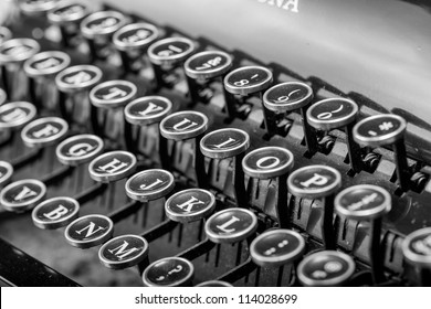 Black and white close up of a vintage typewriter with black and silver keys