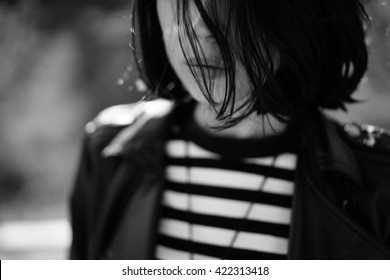 Black and white close-up of black-haired woman with short black hair in sunlight