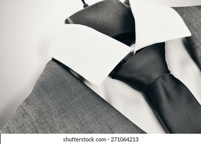 Black and white close-up of an elegant mans suit, collar and tie on clothes hanger on light grey background.