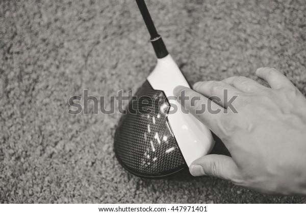 Black and white closeup of a golfers hand using golf club, grass background