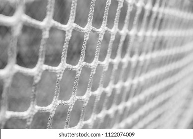 Black and white closeup image of sports netting from a lacrosse goal