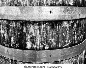 Black and white closeup of an old weathered oak barrel, showing the rough organic texture