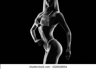 Black and white close-up photo perfect female bikini model posing on black background Attractive female athlete bodybuilder posing demonstrate her well trained body shape arms chest booty Copy space