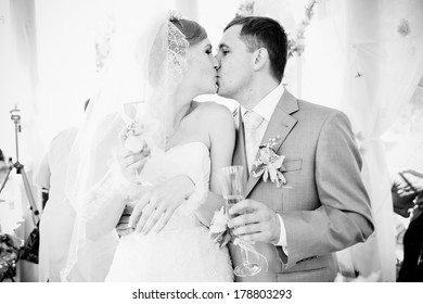 Black and white closeup portrait of bride and groom kissing at alcove