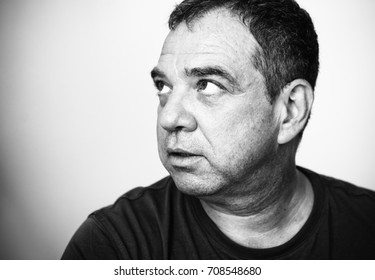 Black and white close-up portrait of a pensive adult man