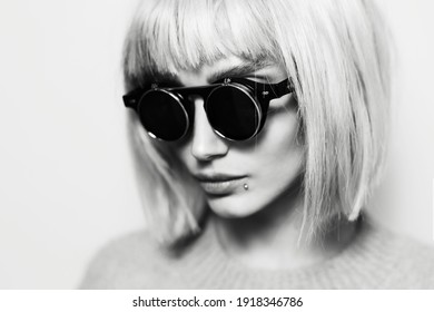 Black and white close-up portrait of young hipster woman wearing round black glasses with bob hairstyle.