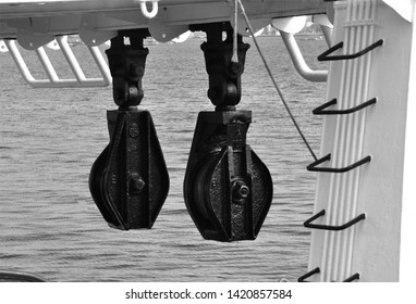 Black and white closeup of two big metal pulleys in a fishing vessel, industrial