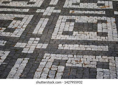 Black and white cobble stones create a geometric pattern. The photo was taken in Prague, Czech Republic.