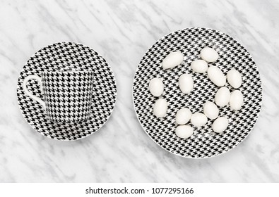 Black and white coffee cup and white chocolate on a plate, on marble background.