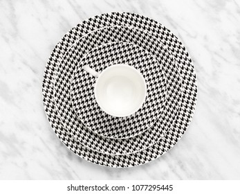 Black and white coffee cup with a set of saucers on marble background.