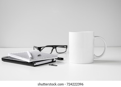 Black and white coffee mug mock up with notebooks, pen and eyeglasses on work desk.