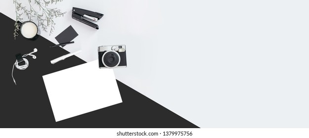 Black and white color background with flower branches, a cup of milk, earphone, pen, stapler, camera, name card and white paper. Architect and designer background with copy space.