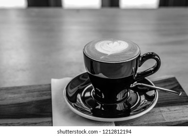 Black and white color of a cup of hot cappuccino coffee on wood table