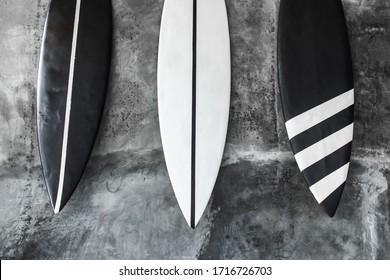 Schwarz-Weiß-Surfbrett auf grauem, betoniertem Hintergrund. Moderne Innenausstattung des Cafés im minimalistischen Stil. Dunkle, schäbige Textur.