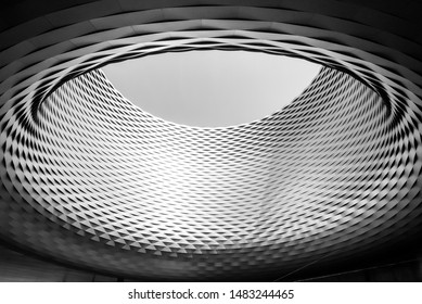 Black and white color and tone, Close up detail of circular architectural shape with woven pattern aluminium panel facade and a big hole on the centre. Messe Basel in Switzerland.