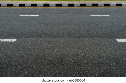 Black and white concrete curb with asphalt road
