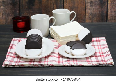 Black and white cookies on a table setting.  Some cookies are upright on a platter and others on a plate.