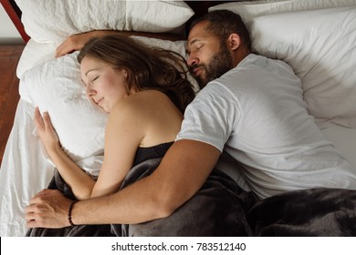 Black and white couple cuddling and sleeping in bed