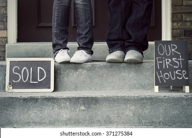 black and white couple on new home doorstep with sold sign and first house sign