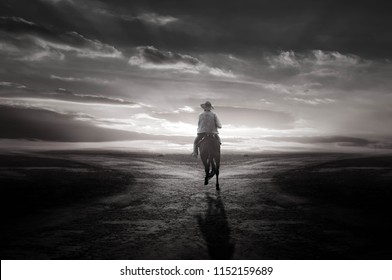 Black and white cowboy riding on the road in the light of the sunset is beautiful.