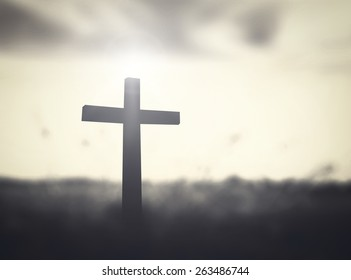 Black and white cross on sunset background, symbol for easter and grace.
