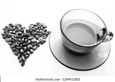 Black and white cup of coffee with heart coffee beans