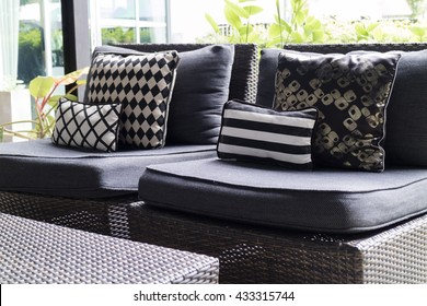 black, white cushion and pillow on wicker rattan chair and desk at terrace