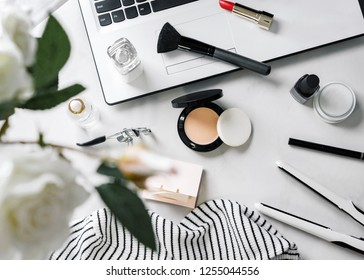 Black and white daily beauty items and lifestyle objects on white marble surface, top view.