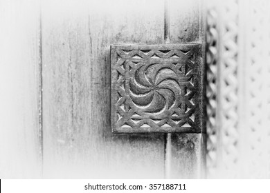Black and white detail of a carving on a traditional wooden Arabian door.