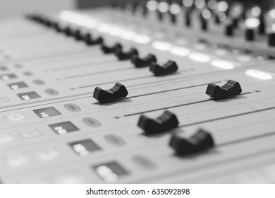 Black and white digital audio sound mixer panel with feyders and adjusting buttons selective focus