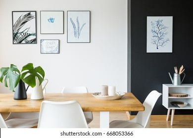 Black and white dining room with wooden table and posters