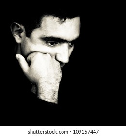 Black and white  dramatic close-up  of a man thinking with a fist on his chin emerging from a black background