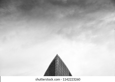 Black and white dramatic cumulonimbus stormy clouds over the roof top of geometrical modern architecture building